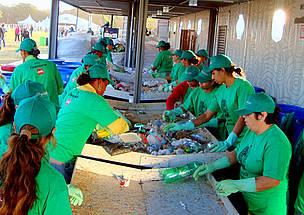 Catadores separando materiais recicláveis em galpão de triagem