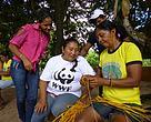 A agricultora Maria Imaculada, da Barra de São Manoel, assiste a confecção de artesanato feita por uma comunitária paraense